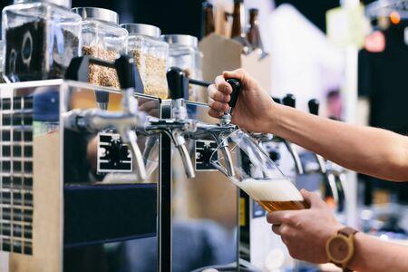 Barkeeper, der beim Bierfest Craft Beer aus einem Hahn gießt. Konzentrieren Sie sich auf Glas und tippen Sie auf Standard-Bild