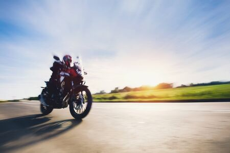 Drive a motorbike. Fast motorcycle in motion on asphalt road. Sunset sky