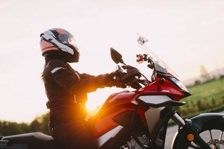 Woman riding motobike at sunset. Sun shining Фото со стока