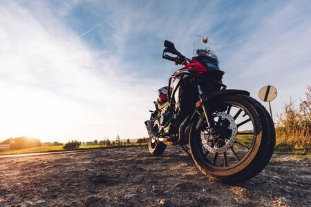 Adventure motorbike on roadside at sunset. Offroad trip. Low angle view