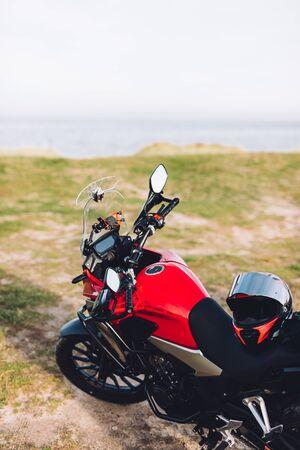 Adventure motorbike on grassy roadside with the ocean view. Offroad trip. 写真素材