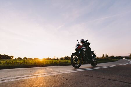 Fast motorcycle drive on asphalt road at sunset. Speed and motion Фото со стока