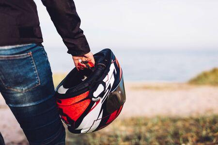 Woman holding a helmet on a motorbike offroad trip break. Ocean view