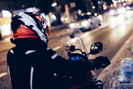 Woman on motorbike in the city at night. About to enter the traffic Banco de Imagens