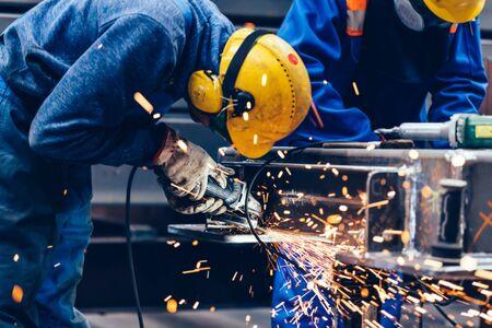Worker grinding in a workshop. Heavy industry factory, metalwork