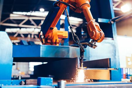 Robotic arm in a factory at work. Modern heavy industry, technology and machine learning