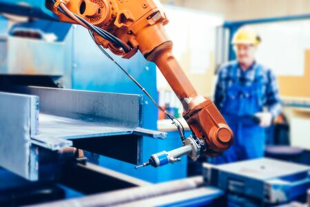 Worker operating robotic arm to cut steel in a factory. Modern heavy industry, technology and machine learning Stock Photo