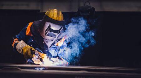 Worker welding in a factory. Heavy industry, welder work Stock Photo