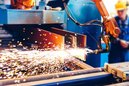 Worker controls robotic arm to cut steel in a factory. Modern heavy industry, technology and machine learning Stock Photo