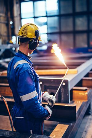 Worker operating acetylene torch in big factory. Heavy industry, shipyard Stock Photo