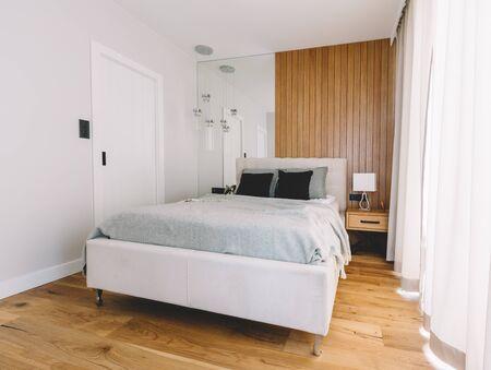 Petite chambre cosy avec lit confortable et parquet. Design d'intérieur moderne et épuré