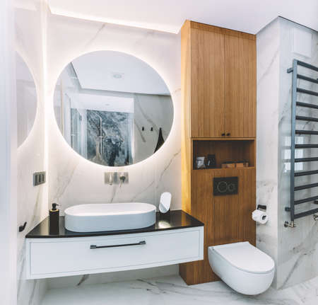 Modern new luxury bathroom. Interior design with marble, wood and stainless steel. Round mirror with led light behind