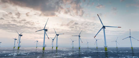 Offshore wind power and energy farm with many wind turbines on the ocean. Sustainable electricity production Stock Photo