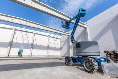 Warehouse construction site. Building a new industrial hall or storehouse. Mobile elavating work platform vehicle
