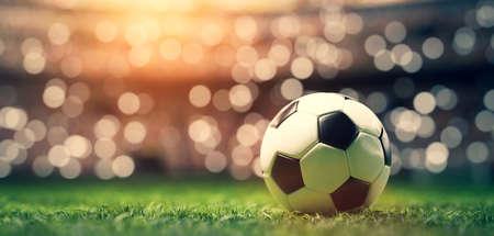 Football soccer ball on grass field on stadium, evening match. Stock Photo