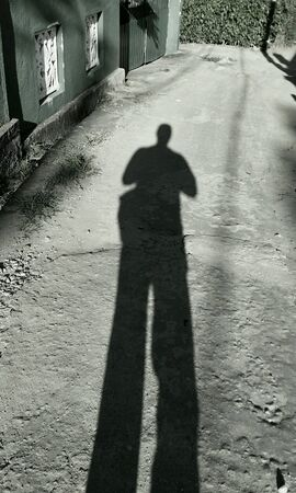 returning: Dark shadow of a man returning home Stock Photo