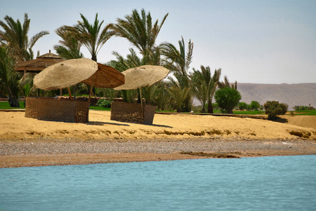 blue lagoon: Beautiful artificial island, blue lagoon, wooden sunbeds Stock Photo