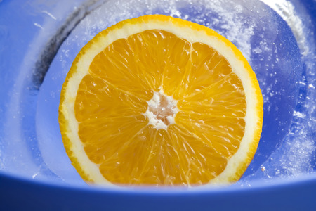 Beautiful view of fresh orange in the ice, blue photo