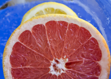 Beautiful view of fresh grapefruit in the ice, blue photo
