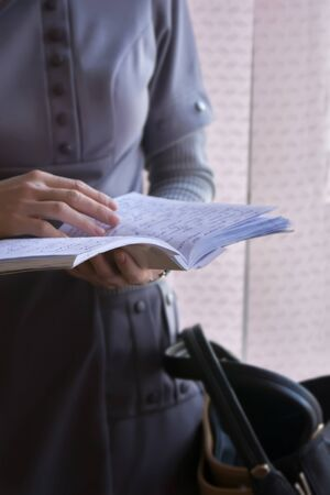revision book: Woman revising notes, note, holding notebook