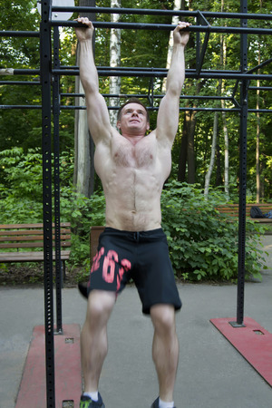 muscularity: Man is training on the horizontal bar, strong body