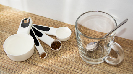 coffee spoon: Glass cup of coffee, spoon, table, sugar