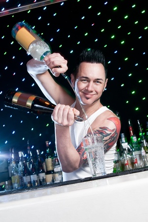 barman: bartender is smiling and looking at the camera