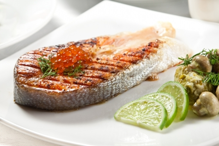Grilled Salmon with Stewed Cabbage, Mushrooms, Garnished with Dill and Red Caviar photo