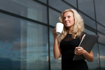 Attractive business lady  with cup of tea is  holding a folder and looking away photo