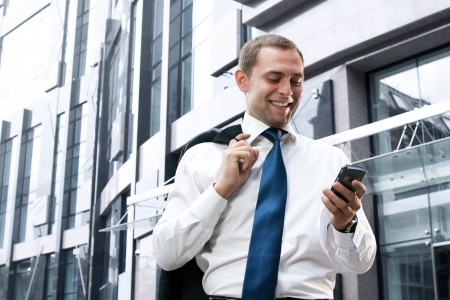 Young and successful businessman is reading a message on his smartphone photo