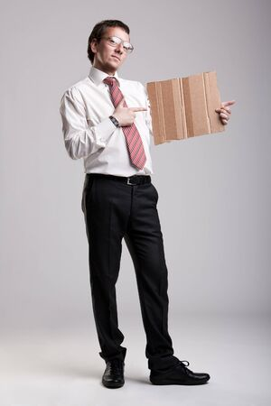 well dressed  holding: Nerdy businessman holding a cardboard Stock Photo