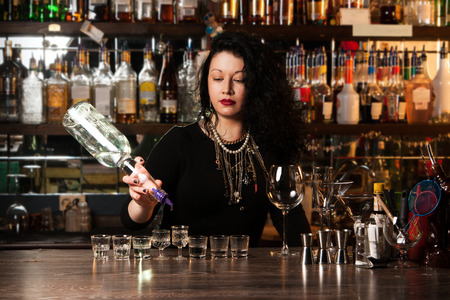 Bartender  pouring alcohol into shot glasses photo