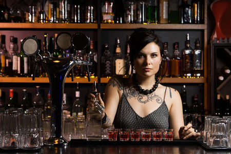 bartender: Attractive bartender with drinks Stock Photo
