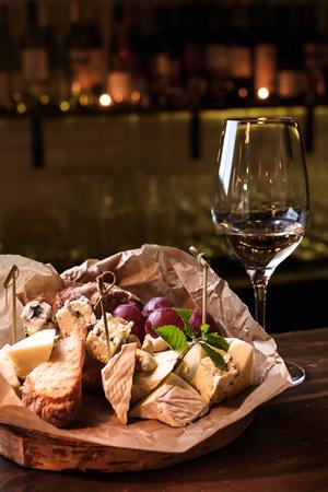 barra de bar: Tabla de quesos y una copa de vino