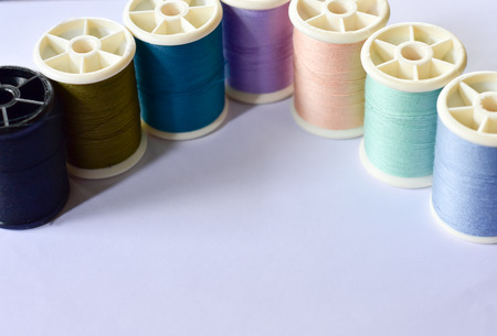 The multi-colored thread is a tailors sewing device, which has a white background.