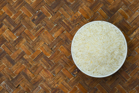 The bowl is filled with white rice and placed on a peasants wooden tray. Banco de Imagens