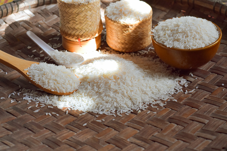 Rice in bowl, rice in a spoon, rice in a crab, jasmine rice is on a wooden floor with light as a background. Banco de Imagens