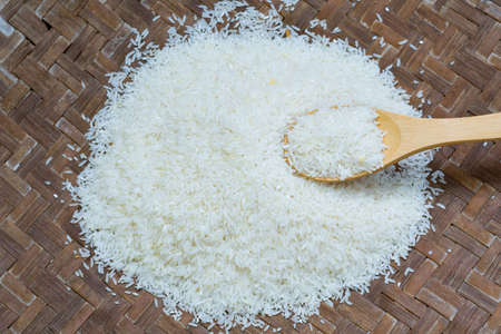 Rice is in wooden spoon on the rice as tray background.