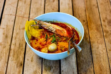 Tom Yum Shrimp Noodles in a bowl background  wooden. Banco de Imagens