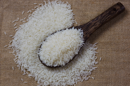 Jasmine rice is on a wooden spoon, beautiful background. Banco de Imagens