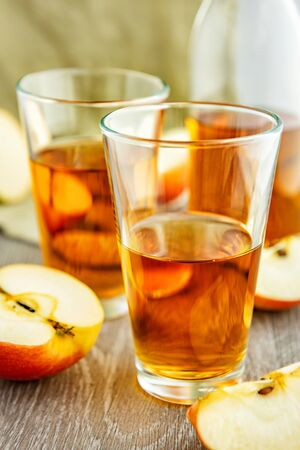 Apple juice in glasses. There are slices of apples and a bottle of juice in the background.