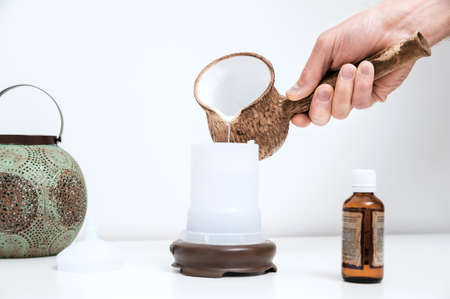 The man's hand is filling with water a capacity of aroma diffuser. Banque d'images