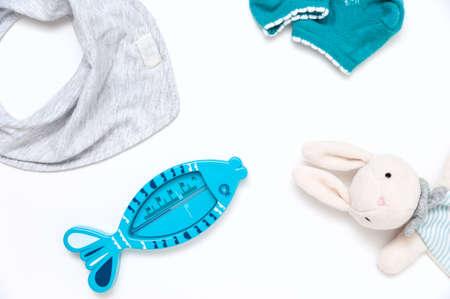 Still life of children's things. Plush toy gloves, bath thermometer, socks, bandana drool bib.