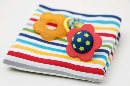 Baby rattles are on a baby blanket.