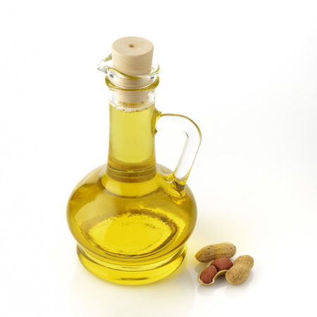 ground nut: Ground Nut Oil with Peanuts on White Background shot  in Studio
