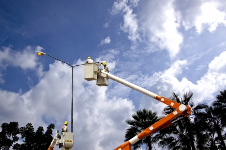 utility pole: Electrician working on power line Stock Photo