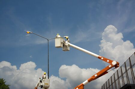 An electrical power utility worker in a bucket fixes the power line