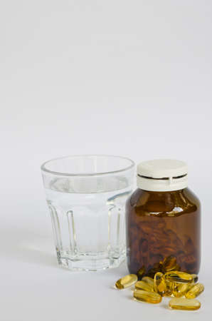 Glass of water and pills on white background photo