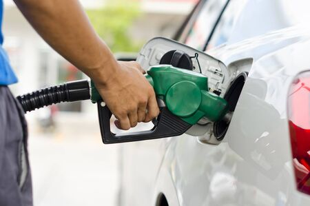 Refueling Car With Gasoline Pump Nozzle, Selective Focus on pump nozzle