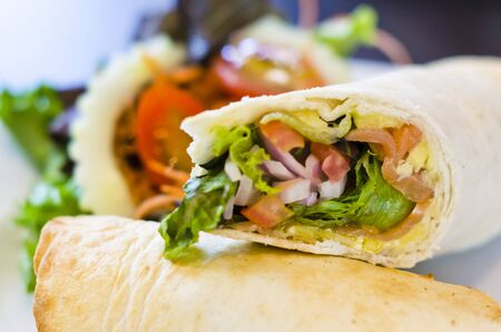 Wrap sandwich with whole wheat tortilla, lettuce, sliced ham, sliced cheese Stock Photo
